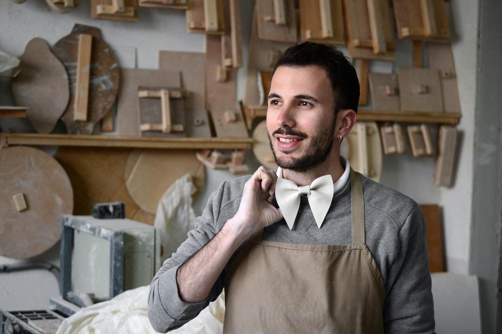 Luis Torres Ceramics en su taller con una de sus pajaritas de cerámica Bowtery en el proceso de realización a mano.