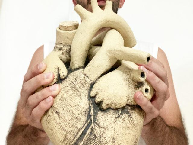 Luis Torres Ceramics sostiene su escultura Corazón de Vino en sus manos alfareras