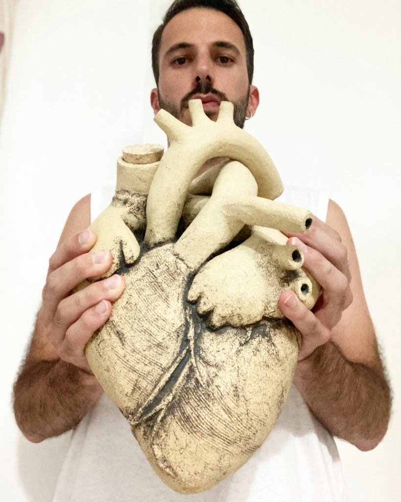 El artista cerámico Luis Torres sostiene su escultura Corazón de Vino.